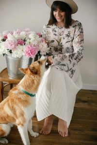 Beautiful hipster woman playing with her pet at big peonies bouquet